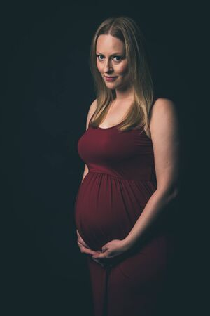 Pregnant woman in red dress holding belly on black background. Portrait of excited, happy, blond, young woman in pregnant studio shoot. Concept of maternity and expectation. Isolated black background. 写真素材 - 134415776