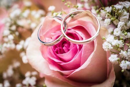 Bruiloft boeket met roze rozen op houten tafel met ringen. Trouwringen en mooi huwelijksboeket op natuurlijk houten bureau met de natuur op de achtergrond. Close-up van roze, paarse en groene bloemen