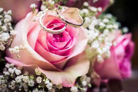 Wedding bouquet with pink roses on wooden table with rings. Wedding rings and beautiful wedding bouquet on natural wooden desk with nature in background. Close up of pink, purple and green flowers 写真素材 - 134415790