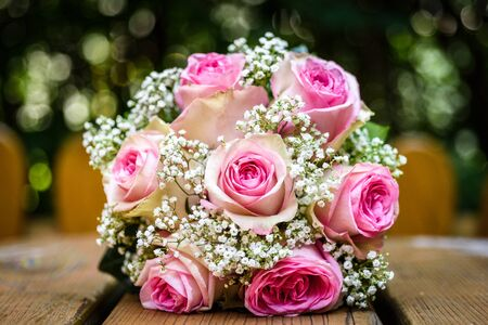 Wedding bouquet with pink roses on wooden table. Beautiful wedding bouquet on natural wooden desk with nature in background. Close up of pink, purple and green flowers. 写真素材 - 134415792