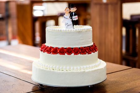 White wedding cake with bride and groom figurines on top. Beautiful white wedding cake with red roses in the table with small husband and wife puppets on top.