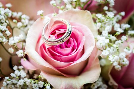 Wedding bouquet with pink roses on wooden table with rings. Wedding rings and beautiful wedding bouquet on natural wooden desk with nature in background. Close up of pink, purple and green flowers