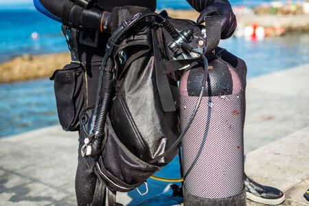 Scuba diver getting ready for scuba diving on the beach. Setting up scuba gear and equipment - steel tank or cylinder, BCD and regulators and getting dressed up before vacation scuba dive.