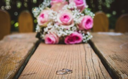 Wedding bouquet with pink roses on wooden table with rings. Wedding rings and beautiful wedding bouquet on natural wooden desk with nature in background. Close up of pink, purple and green flowers 写真素材 - 134415808