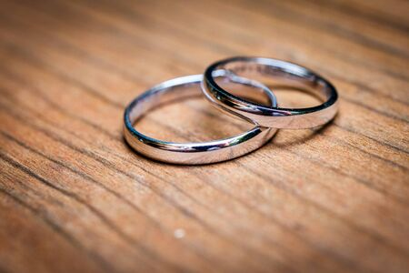 Wedding rings  layingon natural wooden table or desk. Bride and Grooms silver or white gold weddingrings on natural wooden surface. Close up photo. 写真素材 - 134415811