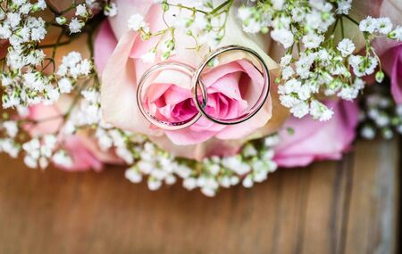 Wedding bouquet with pink roses on wooden table with rings. Wedding rings and beautiful wedding bouquet on natural wooden desk with nature in background. Close up of pink, purple and green flowers 写真素材 - 134415880