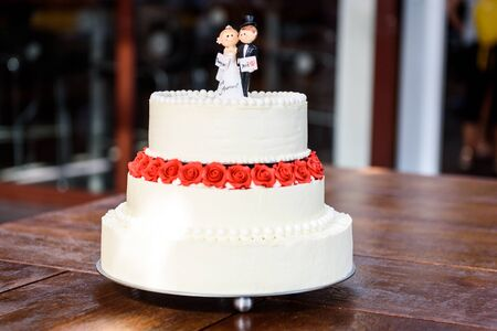 White wedding cake with bride and groom figurines on top. Beautiful white wedding cake with red roses in the table with small husband and wife puppets on top. 写真素材 - 134415884