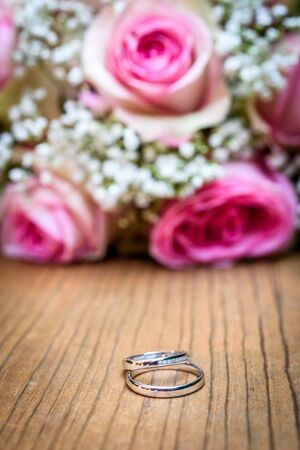 Wedding bouquet with pink roses on wooden table with rings. Wedding rings and beautiful wedding bouquet on natural wooden desk with nature in background. Close up of pink, purple and green flowers 写真素材 - 134415886