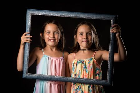 Identical twin girls are making happy expressions with picture frame. Children, sisters, girls posing in studio with picture frame, making different facial expressions. Family portrait, frontal view. 写真素材 - 134415892