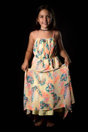 Portrait of happy young little girl holding long colourful dress. Portrait of a cheerful cute little child girl looking at the camera and smiling. Happy children. Isolated on black background. 写真素材