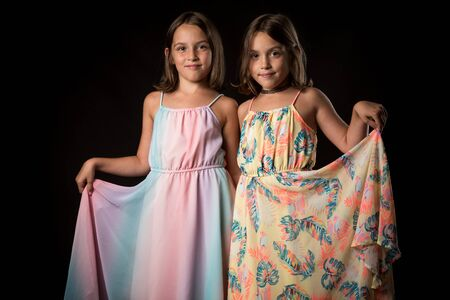 Identical twin girls sisters are posing for the camera. Happy twin sisters in dresses are looking at the camera and smiling. Frontal view, studio shot, isolated on black background. 写真素材 - 134415890
