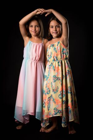 Identical twin girls sisters are posing for the camera. Happy twin sisters in dresses are looking at the camera and smiling. Frontal view, studio shot, isolated on black background.