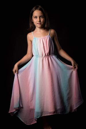 Portrait of happy young little girl holding long colourful dress. Portrait of a cheerful cute little child girl looking at the camera and smiling. Happy children. Isolated on black background. 写真素材 - 134415898