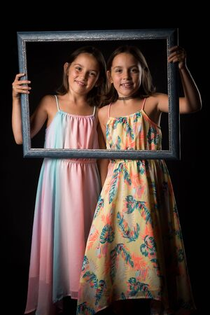 Identical twin girls are making happy expressions with picture frame. Children, sisters, girls posing in studio with picture frame, making different facial expressions. Family portrait, frontal view. 写真素材 - 134415987