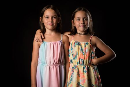 Identical twin girls sisters are posing for the camera. Happy twin sisters in dresses are looking at the camera and smiling. Frontal view, studio shot, isolated on black background. 写真素材 - 134415981