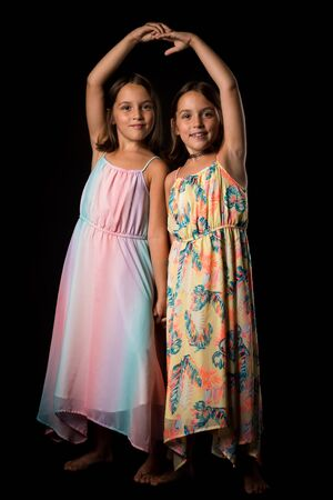 Identical twin girls sisters are posing for the camera. Happy twin sisters in dresses are looking at the camera and smiling. Frontal view, studio shot, isolated on black background. 写真素材 - 134415985
