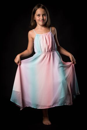 Portrait of happy young little girl holding long colourful dress. Portrait of a cheerful cute little child girl looking at the camera and smiling. Happy children. Isolated on black background. 写真素材 - 134415991