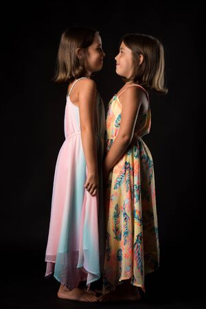 Identical twin girls sisters are posing for the camera. Happy twin sisters in dresses are looking at each other, facing one another and smiling. Frontal view, studio shot, isolated on black background 写真素材
