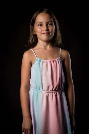 Portrait of happy young little girl holding long colourful dress. Portrait of a cheerful cute little child girl looking at the camera and smiling. Happy children. Isolated on black background. 写真素材 - 134415994