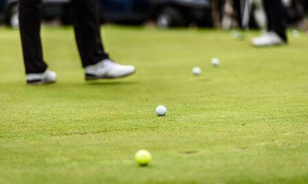 Le gambe del giocatore di golf al torneo di golf praticano lo swing con la mazza da golf. Giocatori di golf sul prato verde che mettono la pallina da golf nel foro. Gara o torneo di golf. Archivio Fotografico