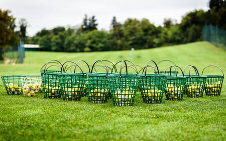 Heap of golf balls in basket ready for warm up. Bunch of golf balls in green basket ready on green morning lawn on golf course intended for players warming up with long drive swing.