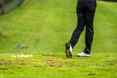 Golfer legs at golf tournament practice swing with driver. Golf player on green lawn putting golf ball in the hole. Golfing competition or tournament.