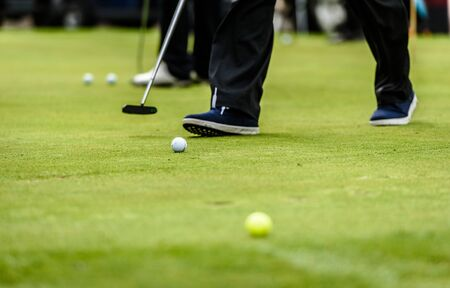 Golfer legs at golf tournament practice swing with golf club. Golf players on green lawn putting golf ball in the hole. Golfing competition or tournament. 写真素材 - 135313223