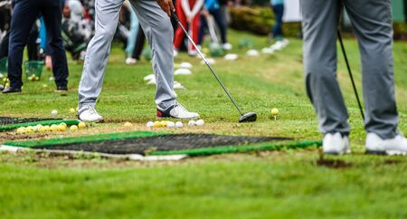 Golfer legs at golf tournament practice swing with driver. Golf players on green lawn putting golf ball in the hole. Golfing competition or tournament.