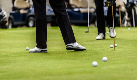 Golfer legs at golf tournament practice swing with golf club. Golf players on green lawn putting golf ball in the hole. Golfing competition or tournament.