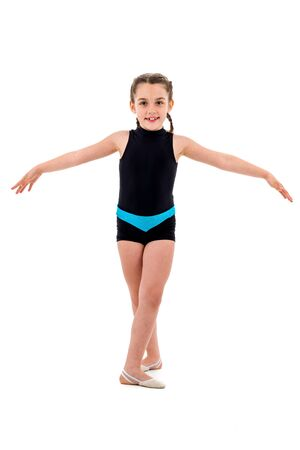 Girl child practice and doing rhythmic gymnastics portrait, white background. Young girl is dancing and having fun performing rhythmic gymnastics exercises. Isolated on white background. Фото со стока
