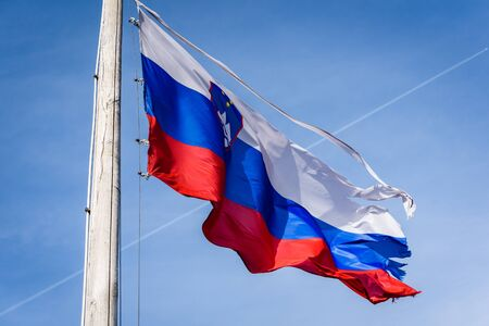 Torn and worn out Slovenian flag waving in the wind. Damaged, worn out, ripped fabric of Slovenia flag is waving in strong winds with blue skies and contrail in background. Stockfoto