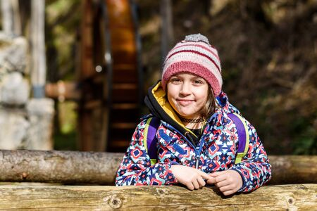Portrait of little girl on hiking forest trip and watermill. Winter portrait of girl on family hike and water mill, active family, parents and children mountaineering in the nature.