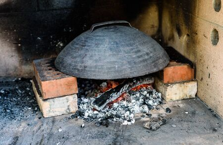 Making of homemade Italian pizza in fireplace brick oven. Making of traditional pizza in stone brick fireplace with fire wood and coals.Heating up a metal lid called sach.