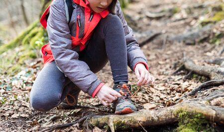 Portrait of girl on hiking forest trip tying shoe laces. Winter portrait of girl on family hike and water mill, active family, parents and children mountaineering in the nature.