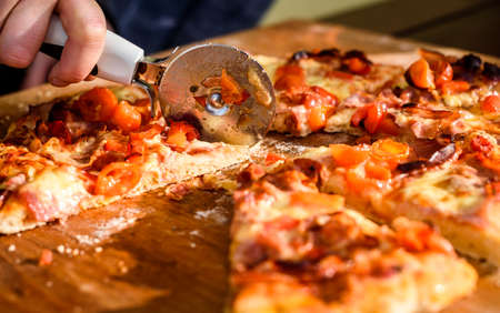 Making of homemade Italian pizza in fireplace brick oven. Making of traditional pizza in stone brick fireplace with fire wood and coals. Cutting finished tasty pizza is perfectly baked with fire.
