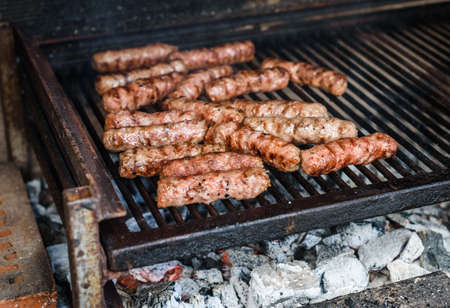 Grilling Meat on barbecue grill with hot coal. Preparing, cooking cevapcici, kebabs, country sausage on charcoal barbecue BBQ in outside fireplace. Traditional Turkish, Bosnian, Serbian, Croatian food Imagens