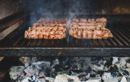 Grilling Meat on barbecue grill with hot coal. Preparing, cooking cevapcici, kebabs, country sausage on charcoal barbecue BBQ in outside fireplace. Traditional Turkish, Bosnian, Serbian, Croatian food 写真素材