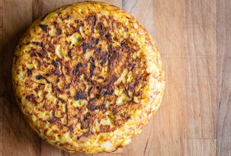 Spanish tortilla, Spanish omelette tortilla de patata. Typical traditional Spanish omelette dish or tapas with eggs, potato, onions andolive oil, served on wooden desk.
