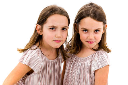 Identical twin girls sisters are posing for the camera. Happy and angry twin sisters in dresses looking at the camera, one laughing one being angry - showing emotions. Studio shot, isolated on white.