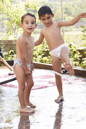 two little boys in panties play with water in the yard Stock Photo - 7650118