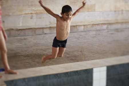 a boy is jumping to the water photo