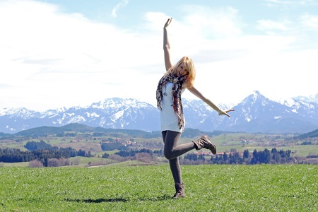 Happy - A young girl is dancing in the spring before the mountains