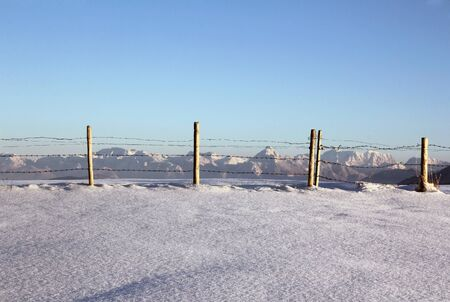 A pristine snowy landscape with the mountains behind the fence Stock Photo - 17560018