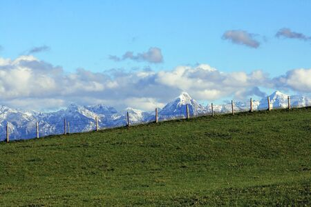 Green fields and snow-capped mountains photo