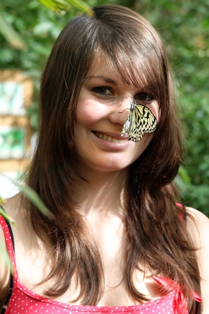 A butterfly lands on the nose of a girl Stock Photo - 18199939