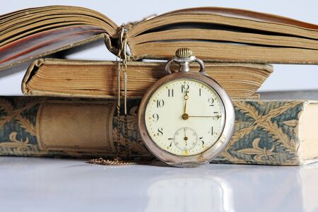 Nostalgia - An old pocket watch and old books photo