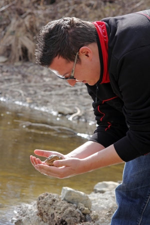 A young man rescues a toad and bring them to the lake photo