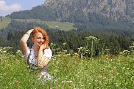 prato montagna: Una giovane ragazza in dirndl nel prato di montagna Archivio Fotografico