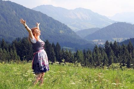 een jonge vrouw in dirndl kijkt uit naar een bergweide Stockfoto