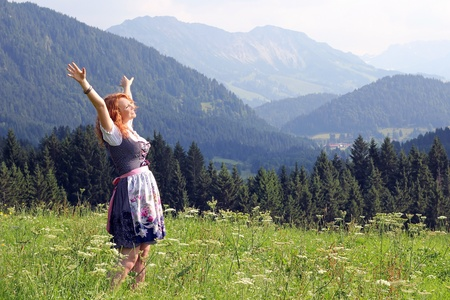a young woman in dirndl looking forward to a mountain meadow